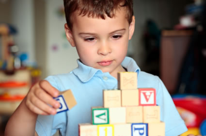 Autistic boy with building blocks  Serotonin signaling in the brain may contribute to autism spectrum disorder